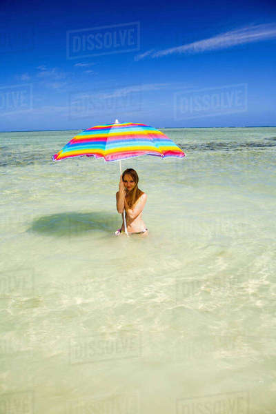 Hawaii, Oahu, Kaneohe, Woman Under A Brightly Colored Umbrella In Crystal Clear Water At The Sandbar Or Dissapearing Island Rights-managed stock photo