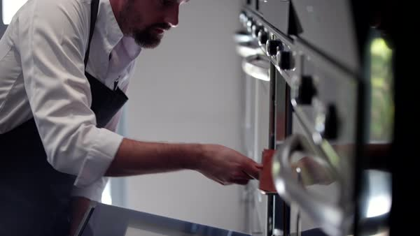 Chef putting tray into the oven. Royalty-free stock video