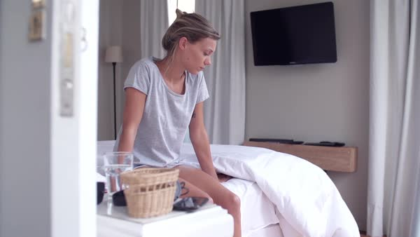 Woman sitting on edge of bed with unhappy expression Royalty-free stock video