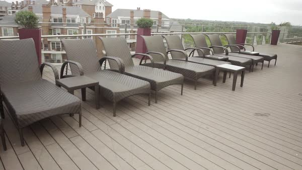 Deckchairs on rooftop poolside overlooking marina at luxury hotel Royalty-free stock video