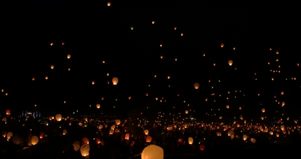 Wide shot of crowd releasing sky lanterns at night Royalty-free stock video