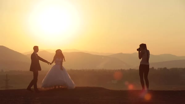 Woman photographer takes photos of wedding couple in the Alpine mountains. Royalty-free stock video