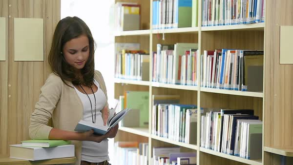 Teenager girl student reading book in college library Royalty-free stock video