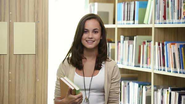 Dolly shot through bookshelf of reading young female student Royalty-free stock video