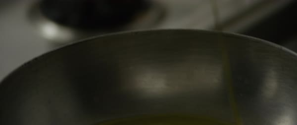 Tilt-up shot of a person pouring olive oil into a frying pan Royalty-free stock video