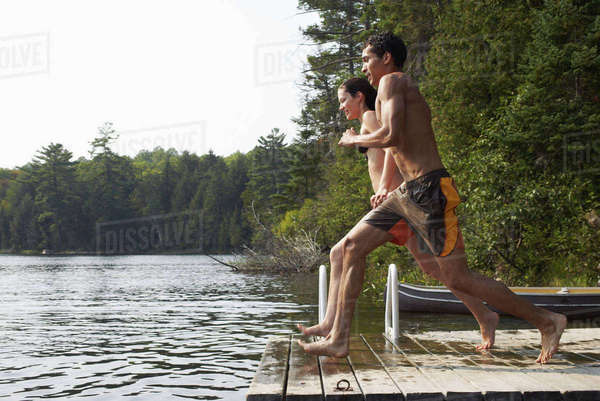 Couple jumping from dock Royalty-free stock photo