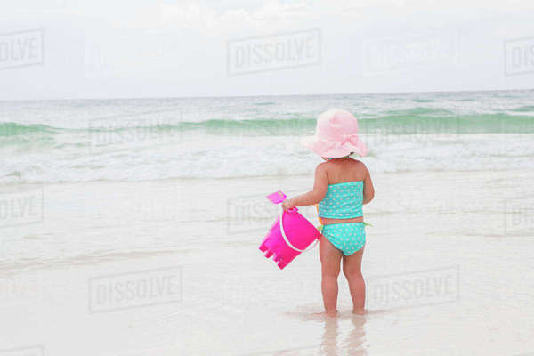 Toddler Girl Playing in Ocean with Shovel and Bucket at Beach, Destin, Florida, USA Royalty-free stock photo
