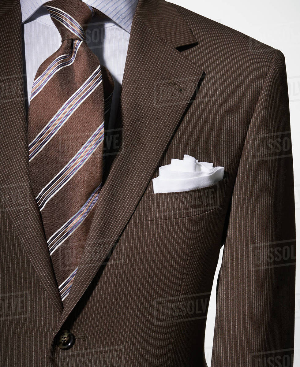 b2c7132dd89fb Detail of a bown suit jacket with shirt, white handkerchief and brown  striped necktie