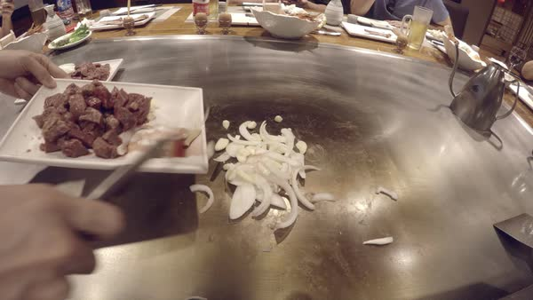 Chef's POV at Japanese teppanyaki restaurant. Cook's view of hibachi food preparation and cooking of steak and onions to serve to guests. Reverse view of teppanyaki chef. Royalty-free stock video