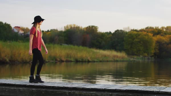 Young, pretty, millennial woman wearing a floppy hat, walks along a dock at a lake  at sunset; she smiles at camera. Royalty-free stock video