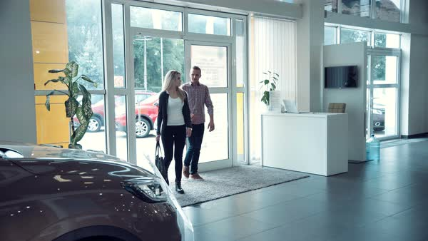 Couple comes into car dealership to shop for a car. The sales manager approaches them. Royalty-free stock video
