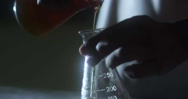 Hand-held shot of a person pouring liquid from one lab flask into another one Royalty-free stock video