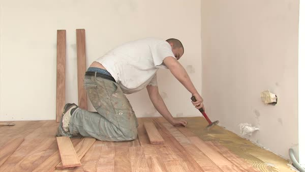 Young Caucasian professional worker fitting hardwood floor with a hammer Royalty-free stock video