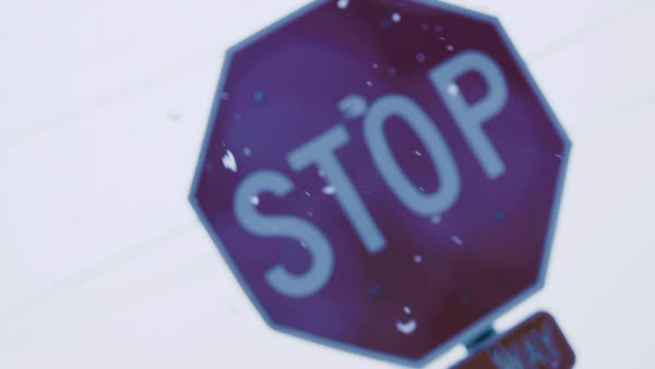 Snow drifting down in front of a stop sign. Royalty-free stock video