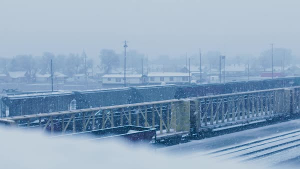 Snow falls overlooking a rail yard. Royalty-free stock video
