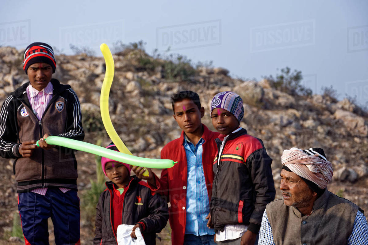 Indian rural boys standing with balloons on hilltop with old man. Royalty-free stock photo