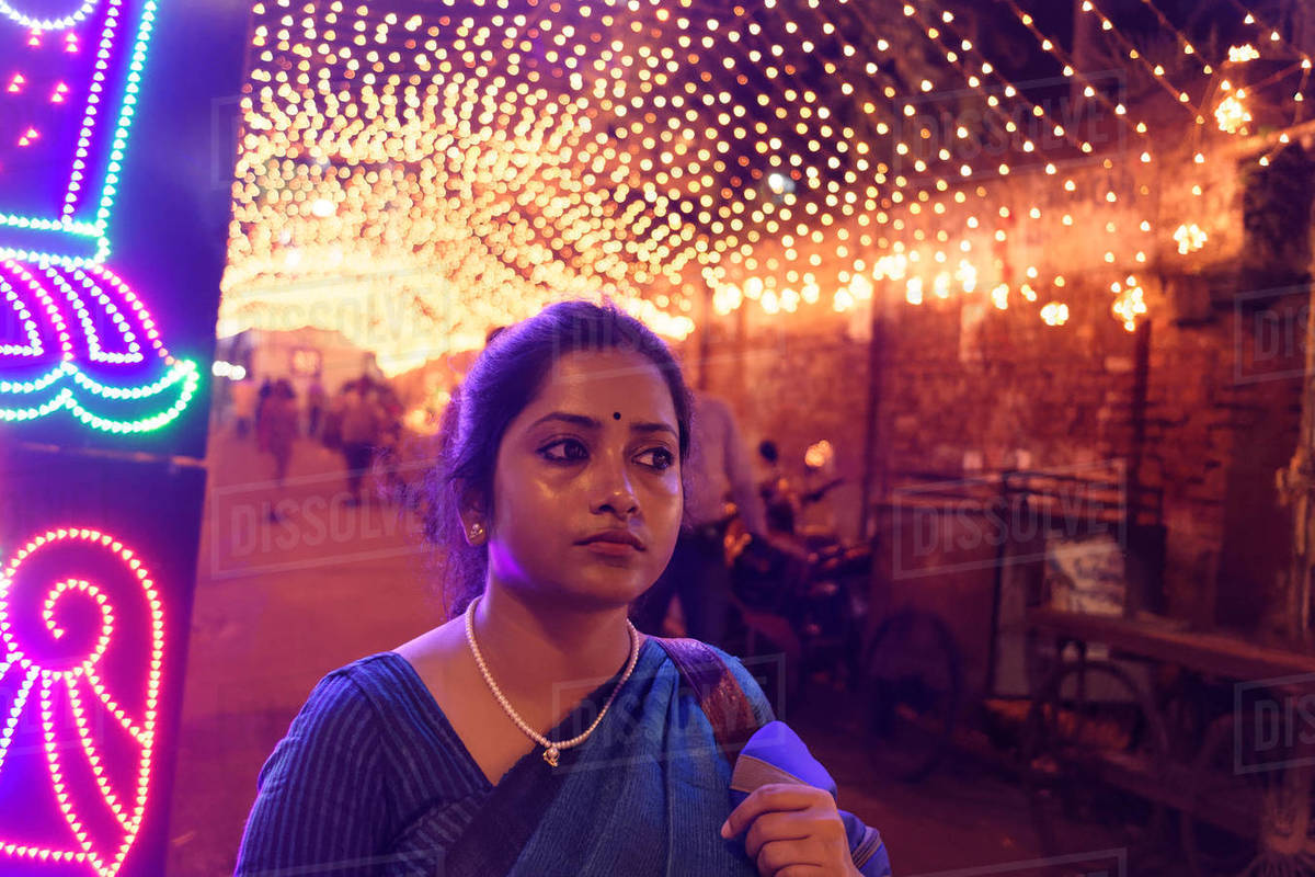 Indian Bengali lady on street full of lights in a festive evening Royalty-free stock photo