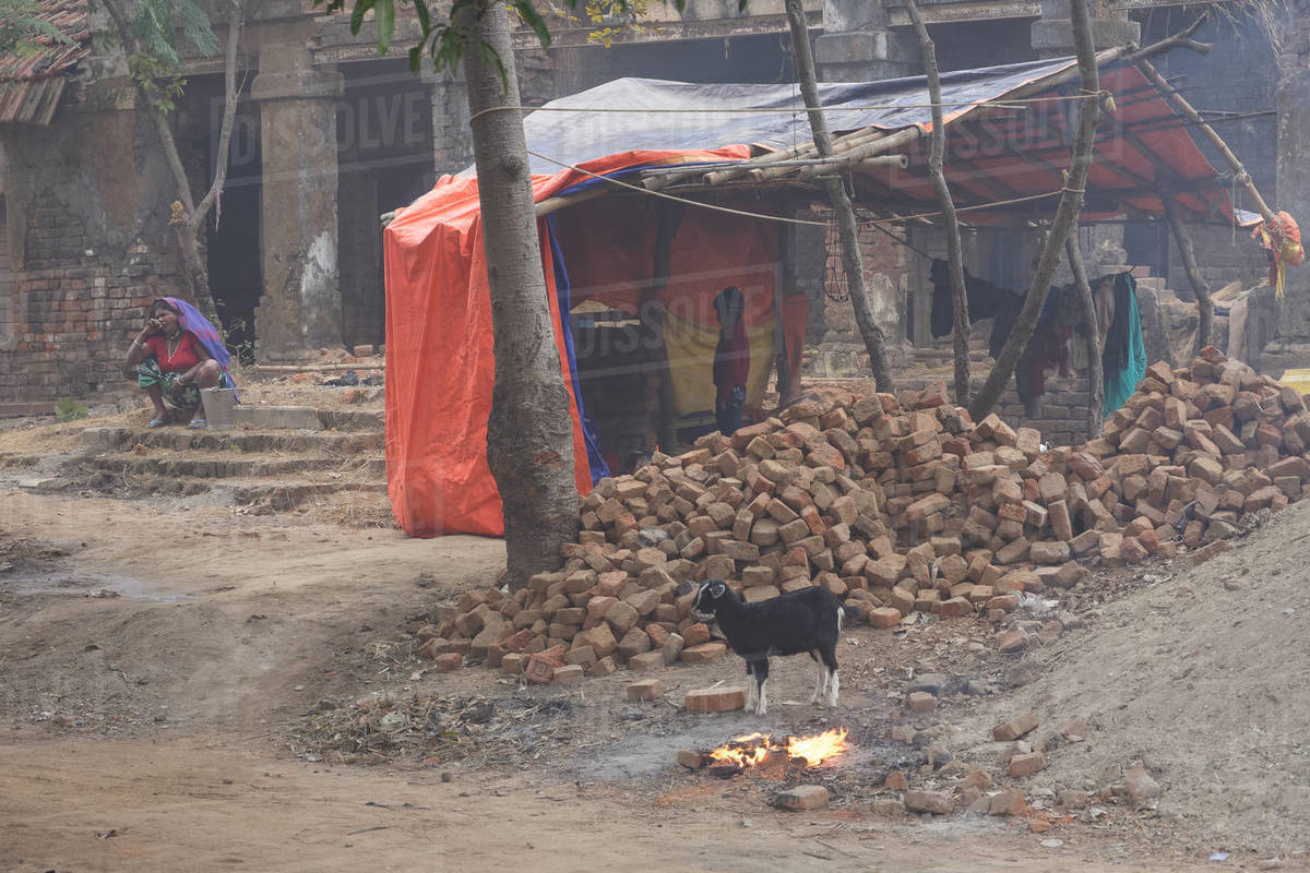 Scene of a early morning in brick storage with fire, goat and people Royalty-free stock photo