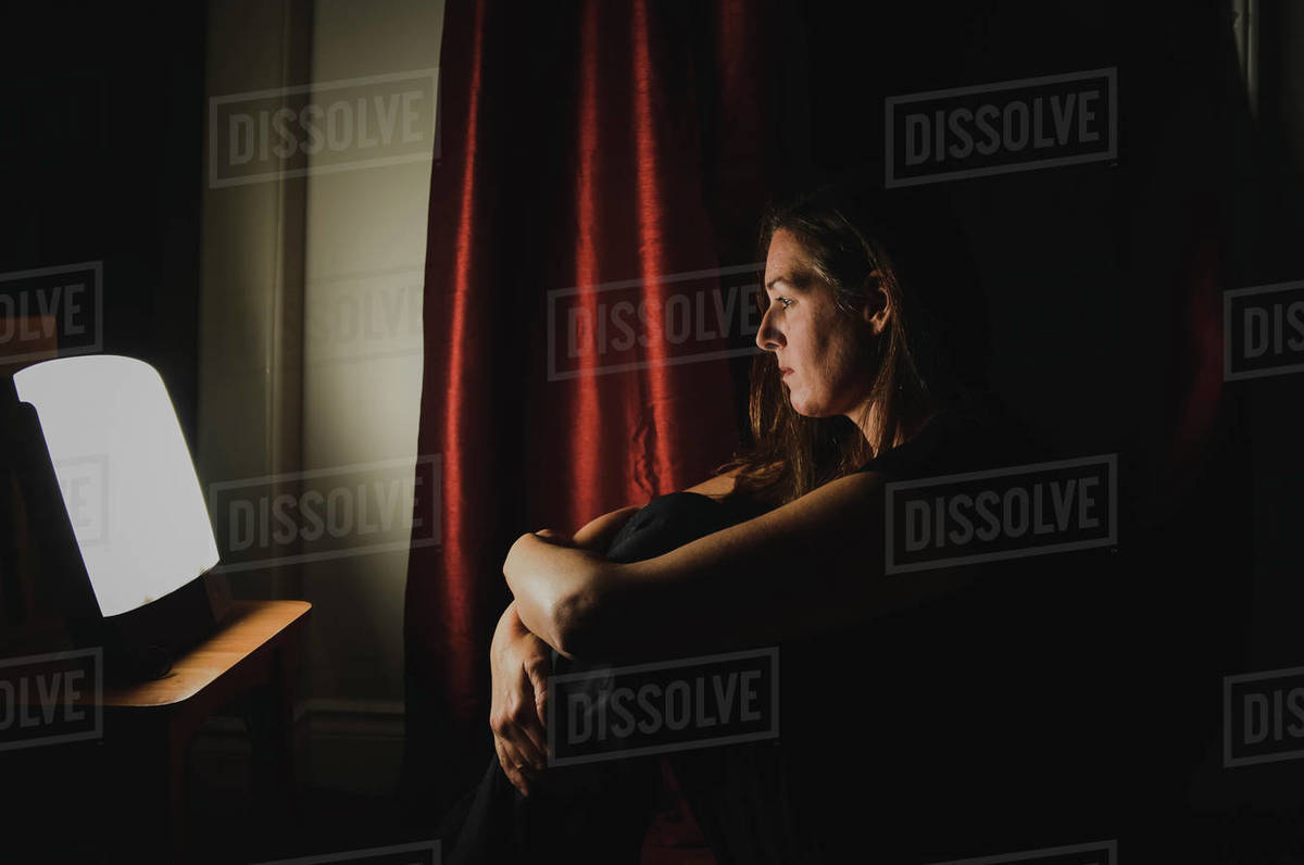 Profile of woman sitting looking at light therapy lamp in a dark room Royalty-free stock photo