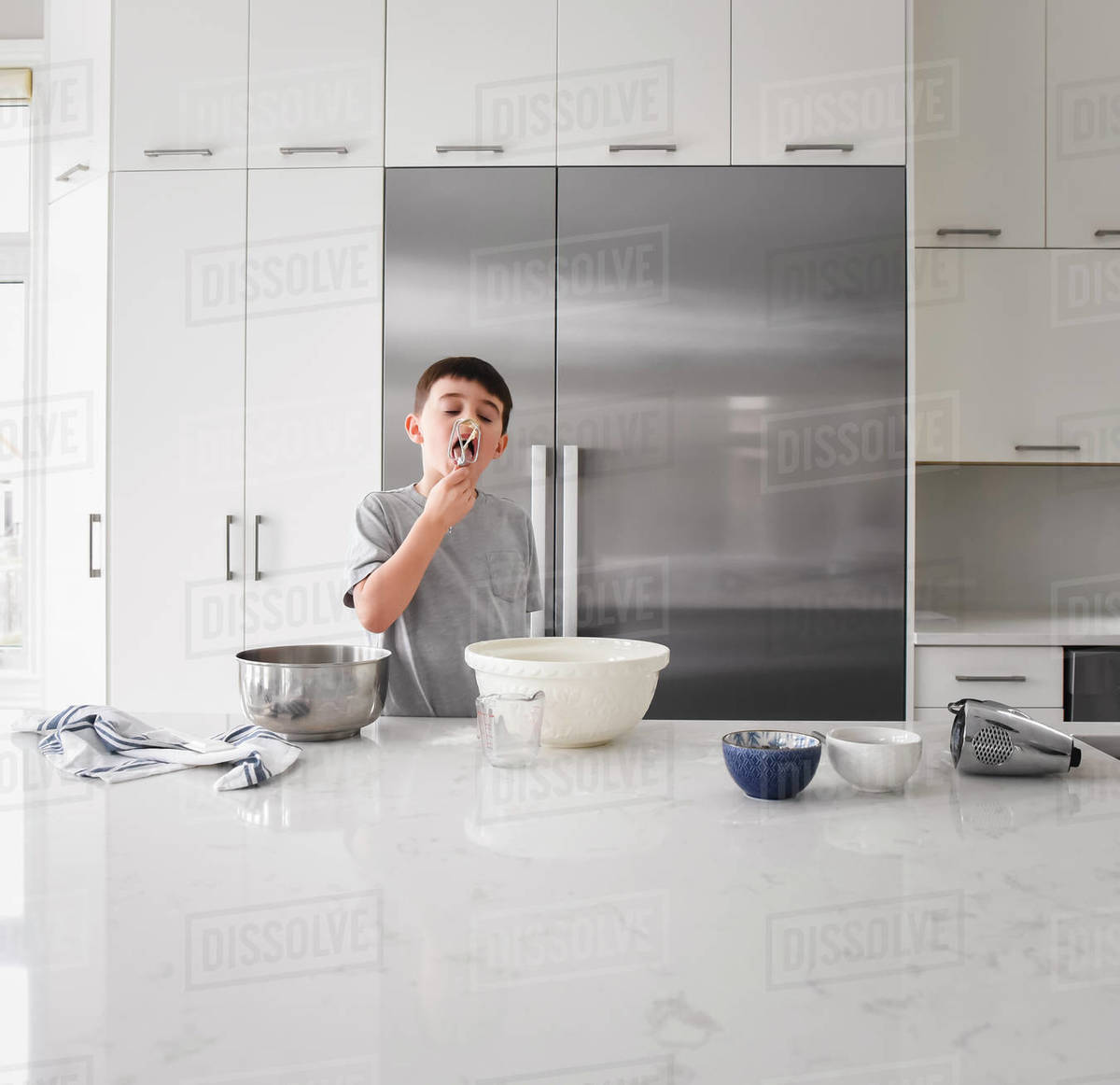Young boy licking batter off of beater in modern kitchen Royalty-free stock photo
