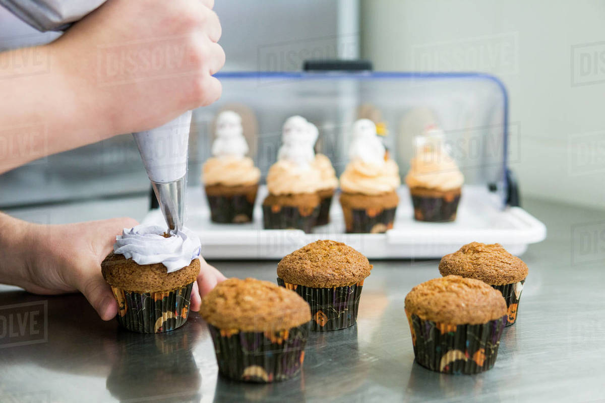 Chef topping cupcakes with homemade butter cream Royalty-free stock photo