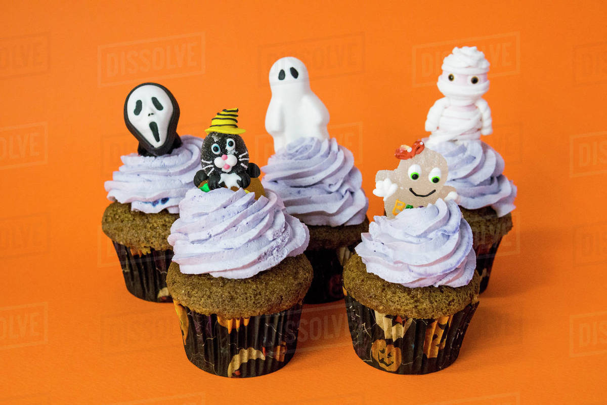 Group of funny halloween monster cupcakes on an orange table Royalty-free stock photo