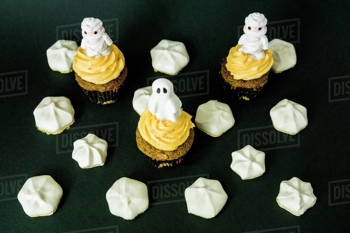 Funny scary cupcakes on a black bacground with meringue all around Royalty-free stock photo