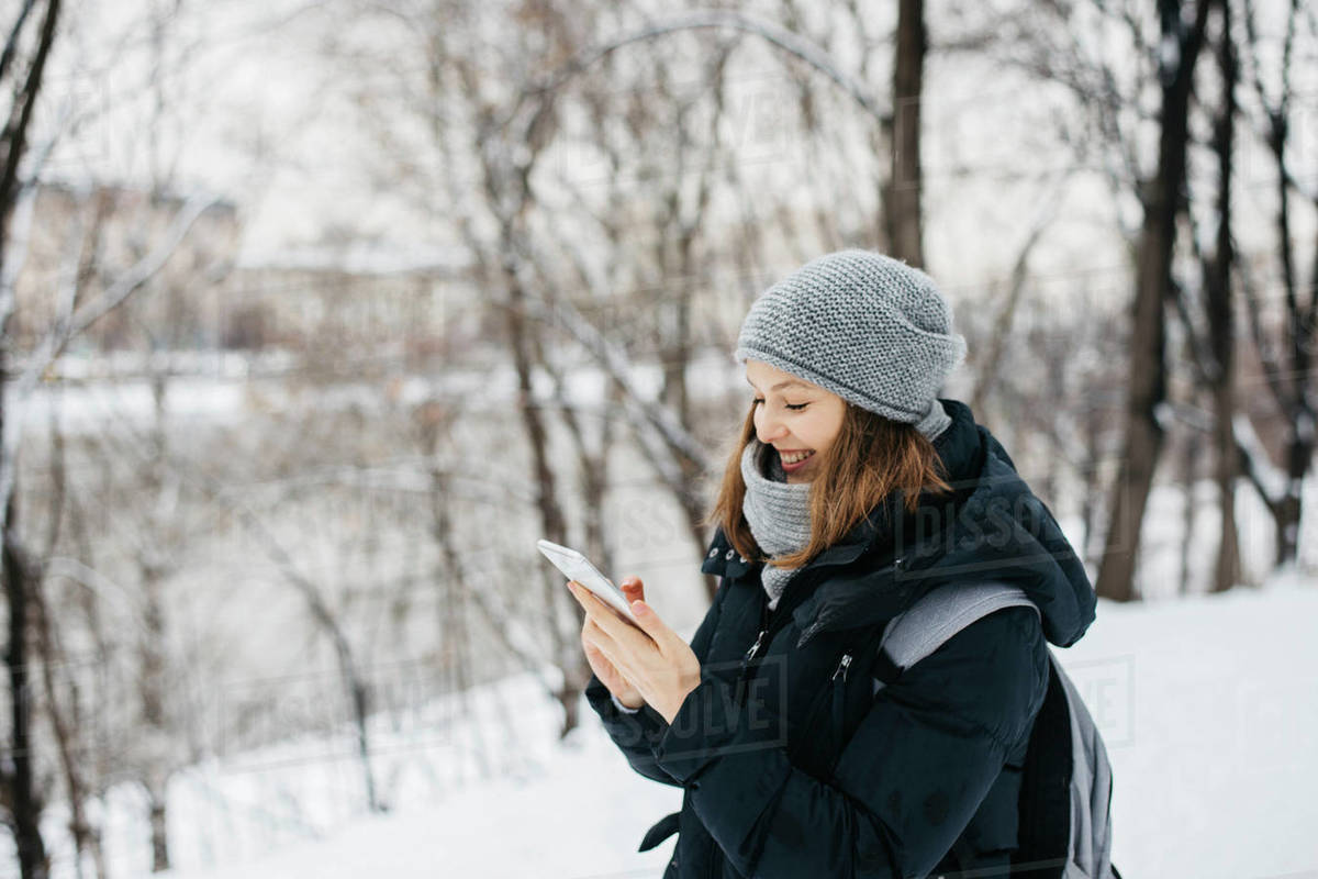 Happy young woman in hat with phone texting outdoors in winter park Royalty-free stock photo
