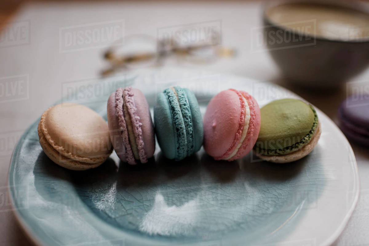 Colourful macarons on plate with a drink Royalty-free stock photo