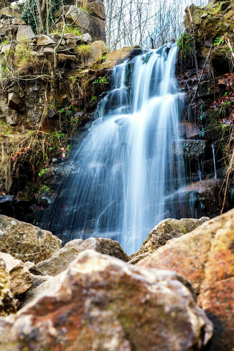 Scenic view of stream flowing against waterfall in forest Royalty-free stock photo