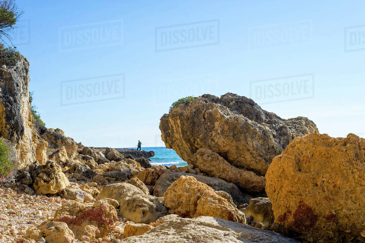 Unrecognizable man standing on the sea rocks while fishing Royalty-free stock photo
