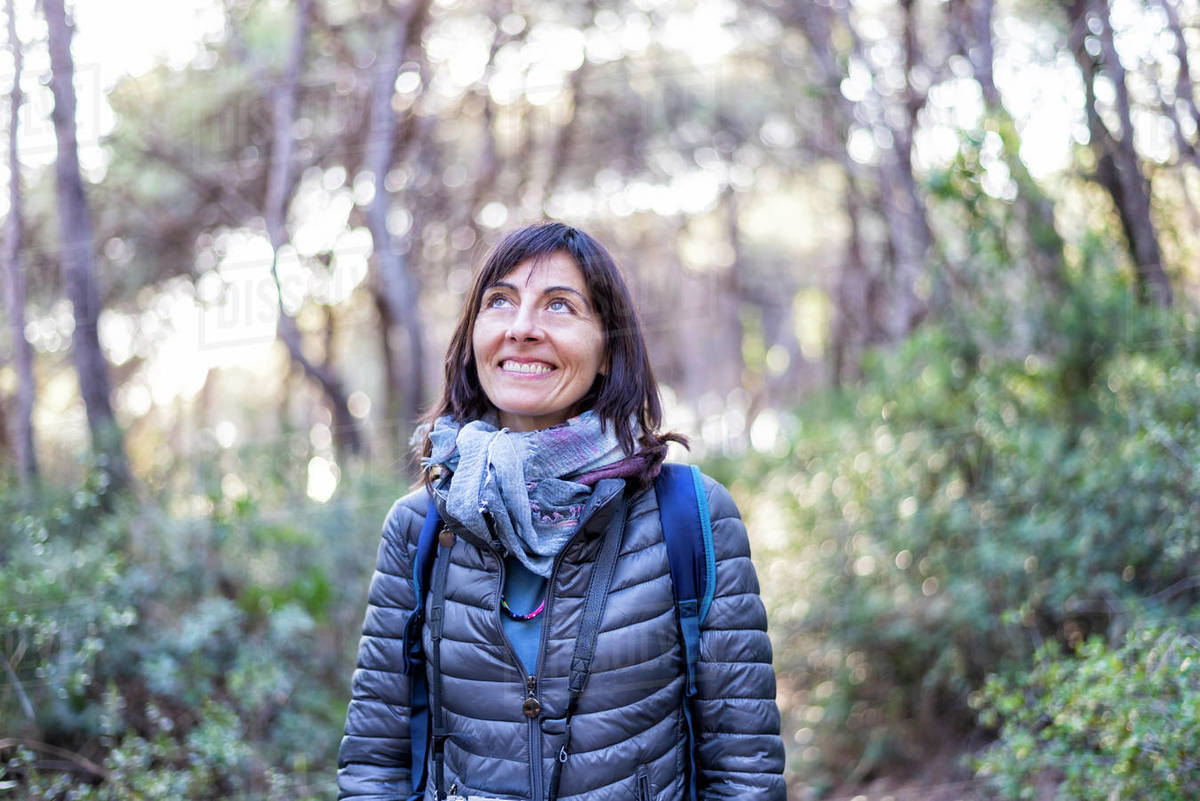 Front view of a backpacker woman smiling while looking up Royalty-free stock photo