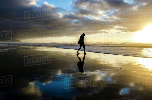 Silhouette woman walking at beach against cloudy sky during sunset Royalty-free stock photo