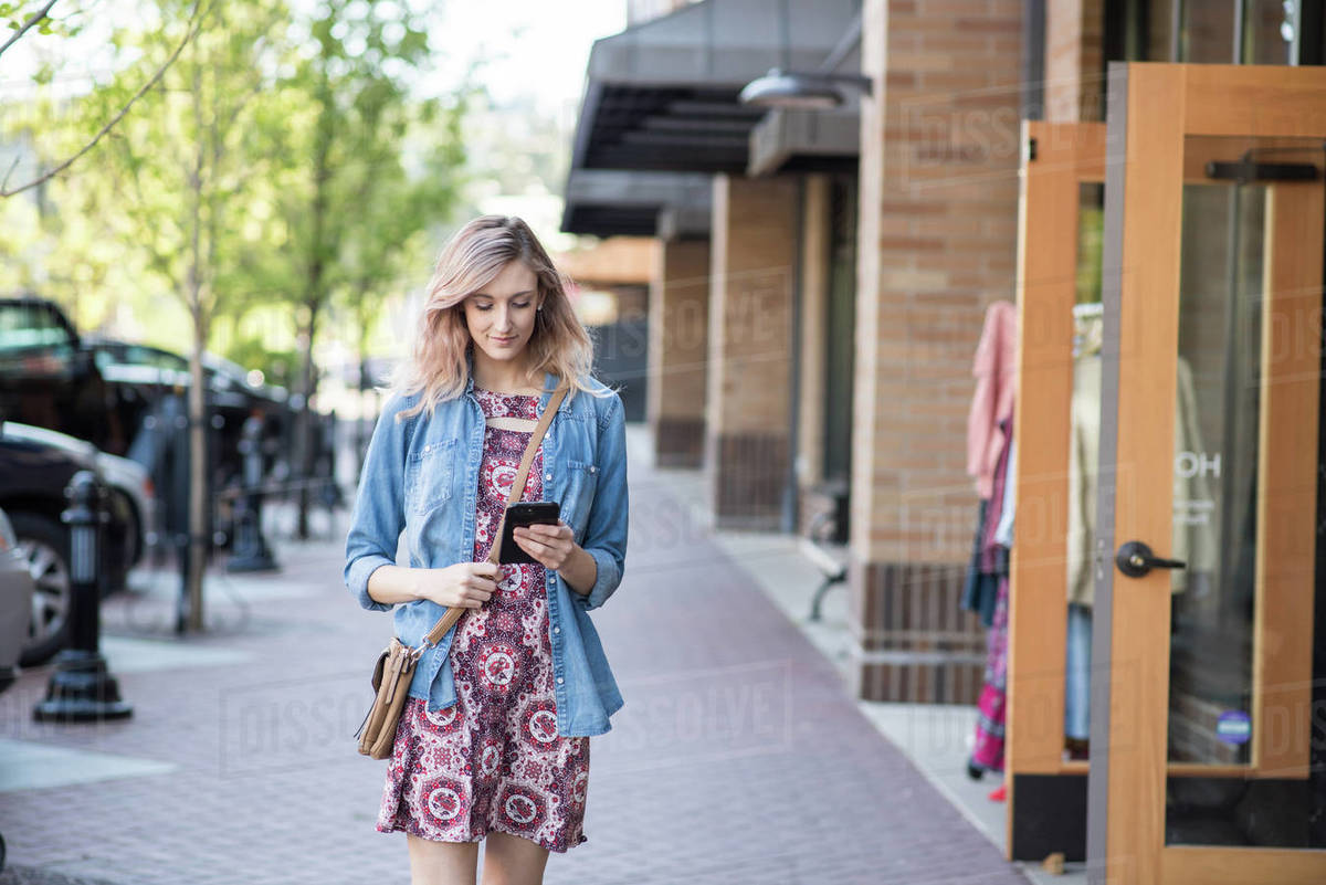 Woman walking down street in front of shop texting on phone Royalty-free stock photo
