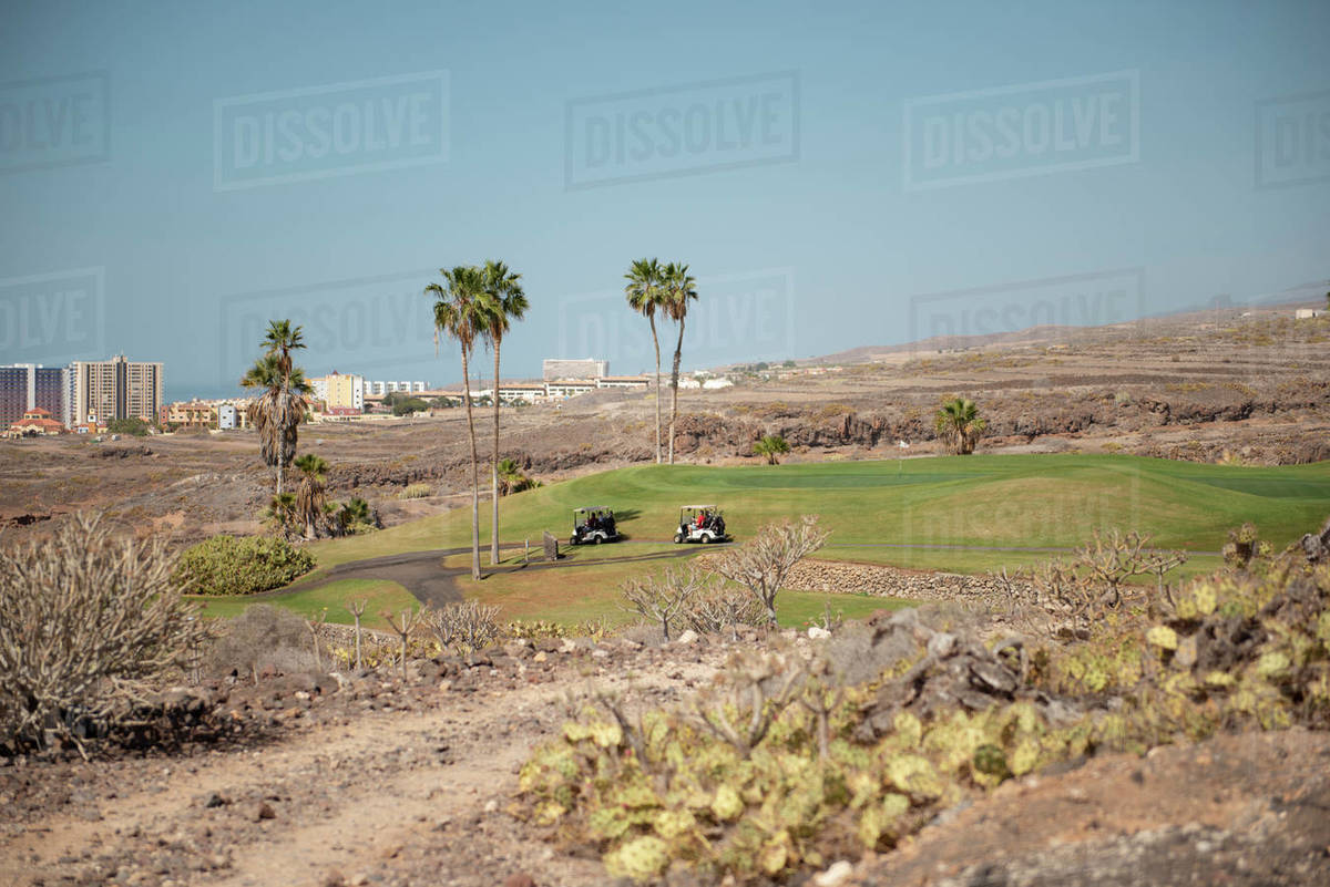 Two golf carts moving on the path of a golf course during sunny day Royalty-free stock photo
