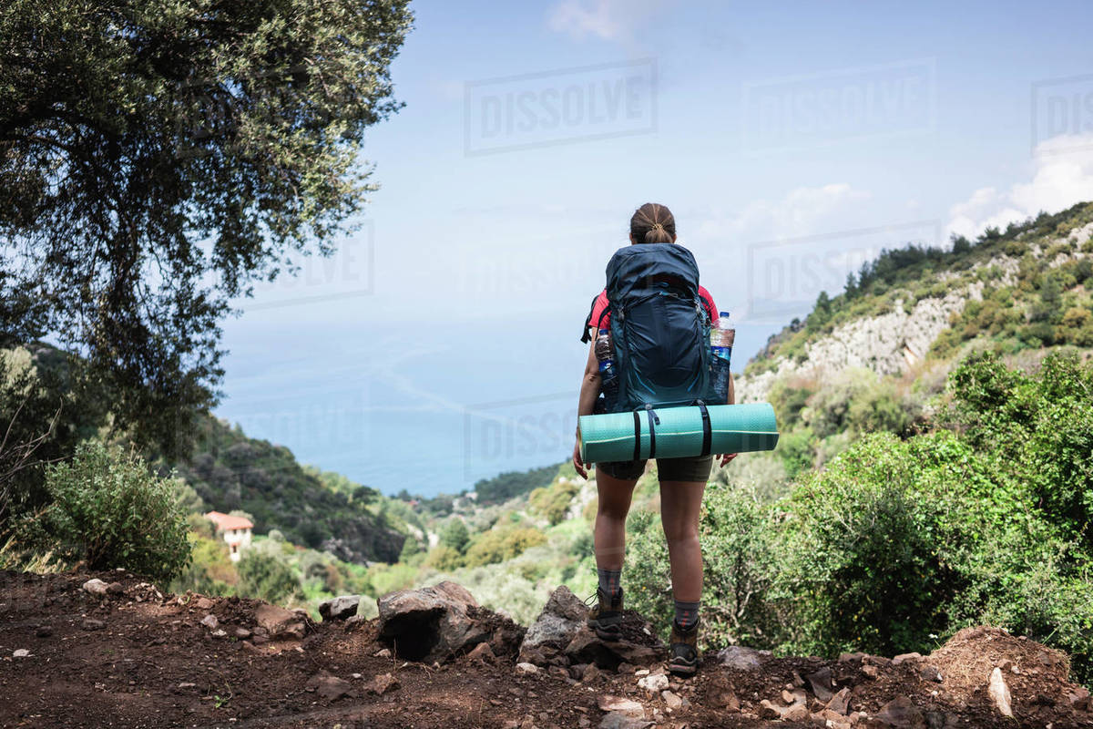 Rear view of young woman standing on the hill and looking at seascape Royalty-free stock photo