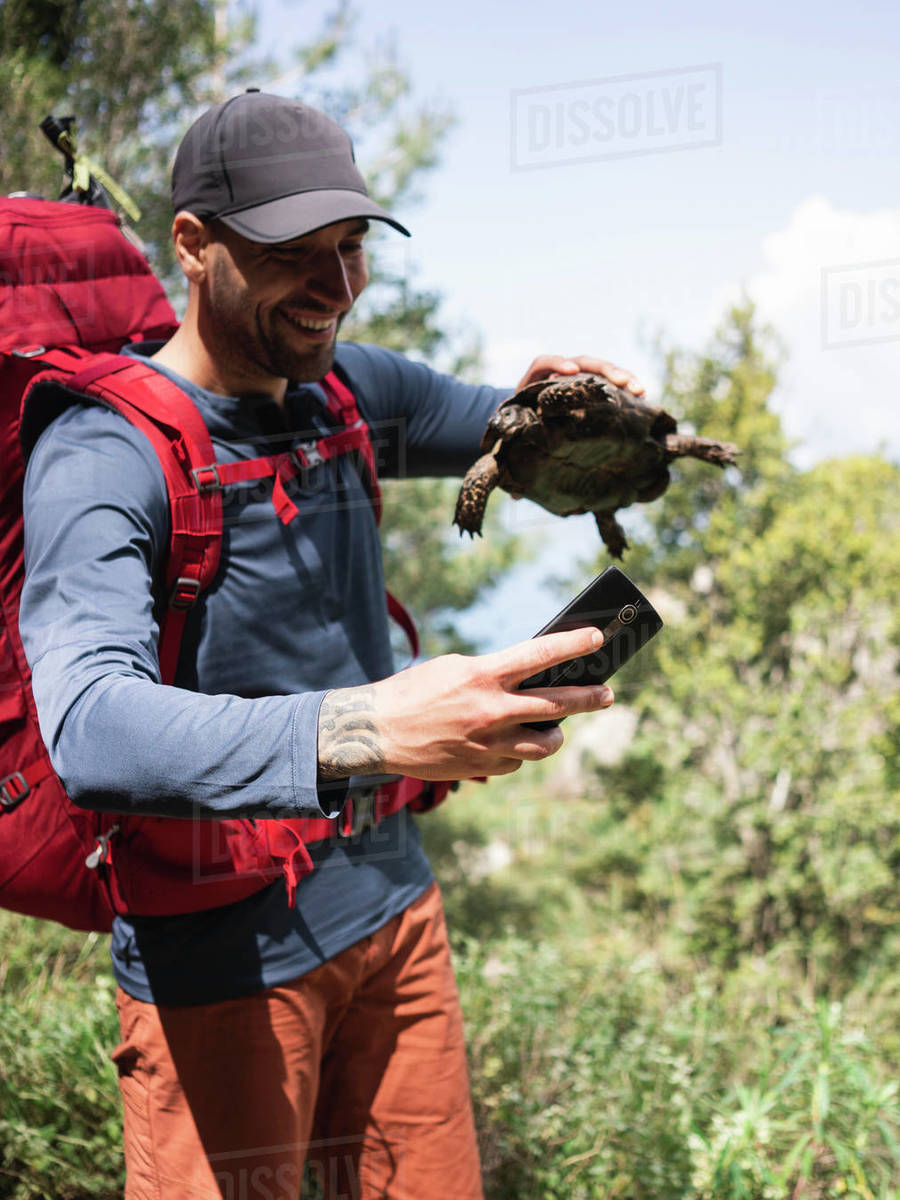 Smiling man making selfie with turtle by mobile phone against sky Royalty-free stock photo