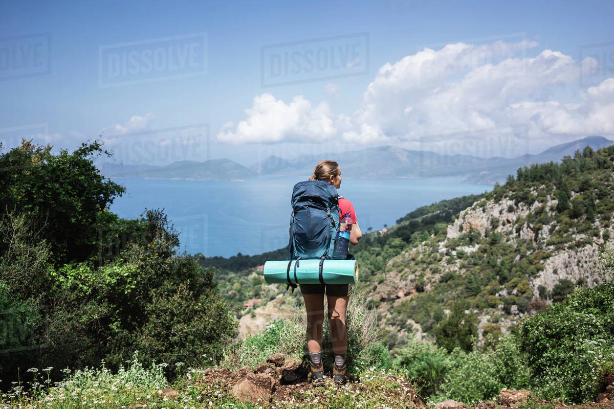 Rear view of woman standing on mountain cliff against seascape and sky Royalty-free stock photo