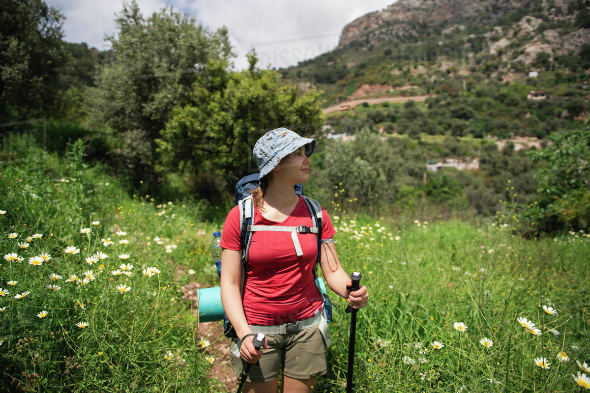 Female hiker standing in chamomile field and enjoying by sunny weather Royalty-free stock photo
