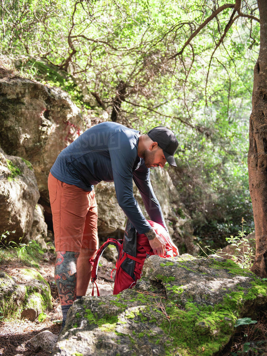 Man preparing backpack for hiking amidst green trees in leaf forest Royalty-free stock photo