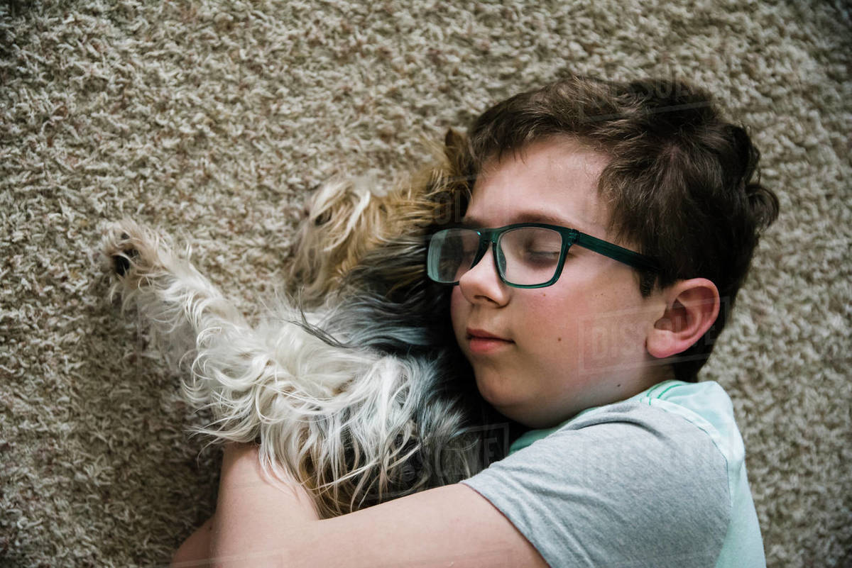 Boy hugging his dog lying on the floor at home. Royalty-free stock photo