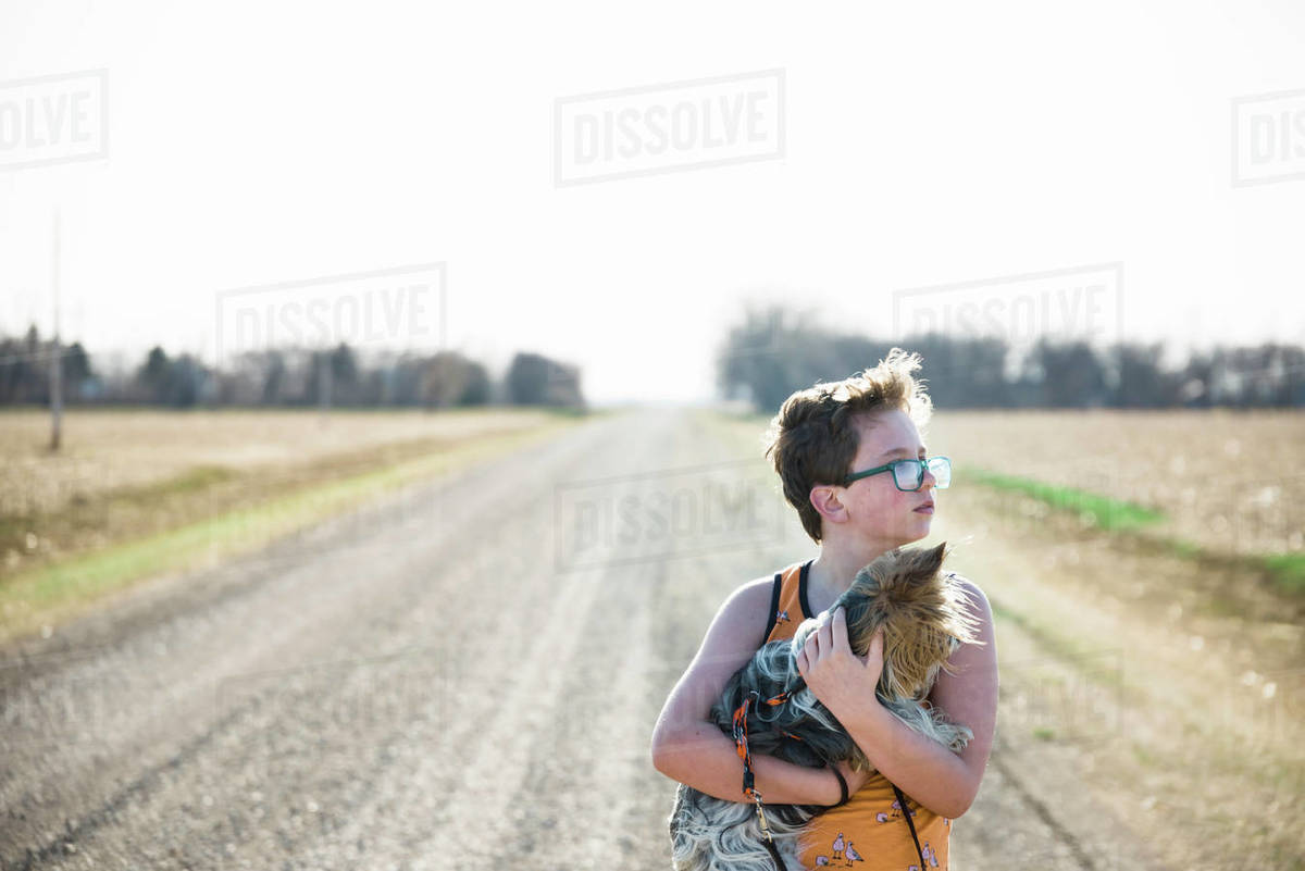 Boy holding his pet puppy in the country on a gravel road. Royalty-free stock photo