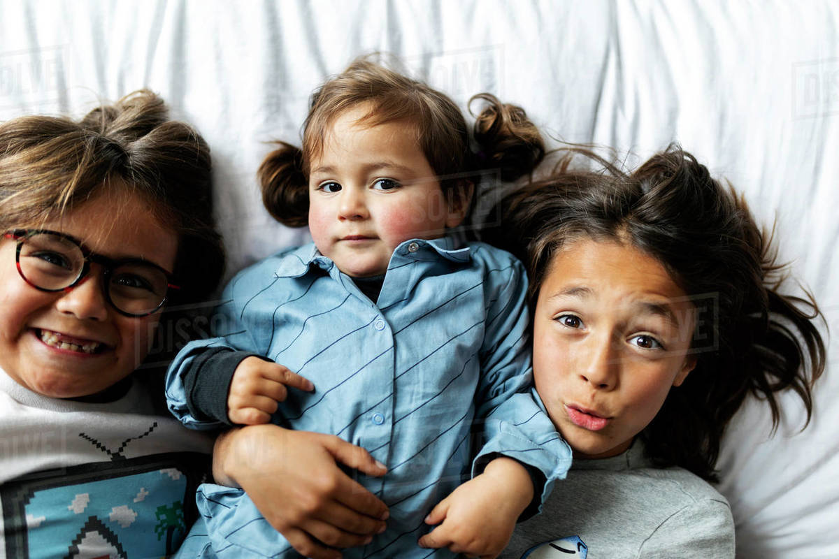 Overhead view of two young boys lying on bed with their sister Royalty-free stock photo