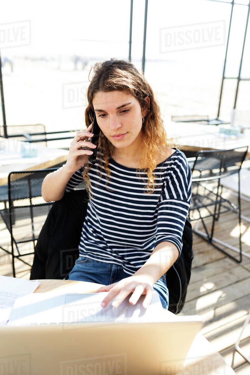 Young beautiful happy woman working with laptop on a terrace Royalty-free stock photo