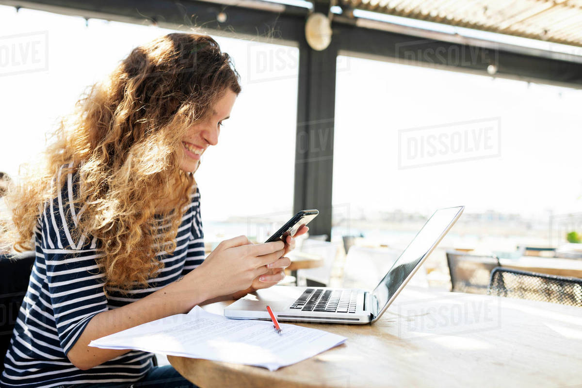 Woman texting while working with laptop on a terrace Royalty-free stock photo