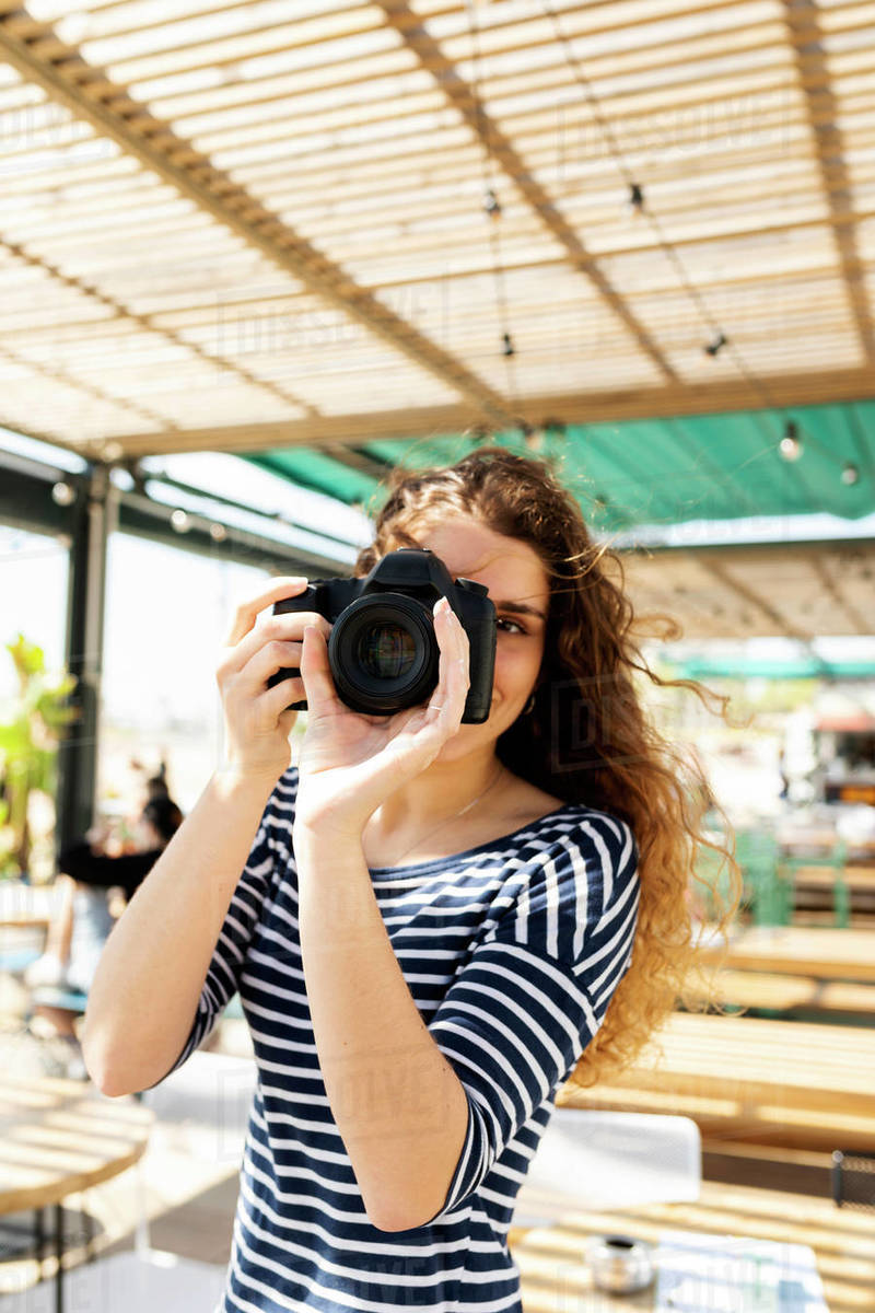 Brunette young woman on beach terrace holding camera Royalty-free stock photo