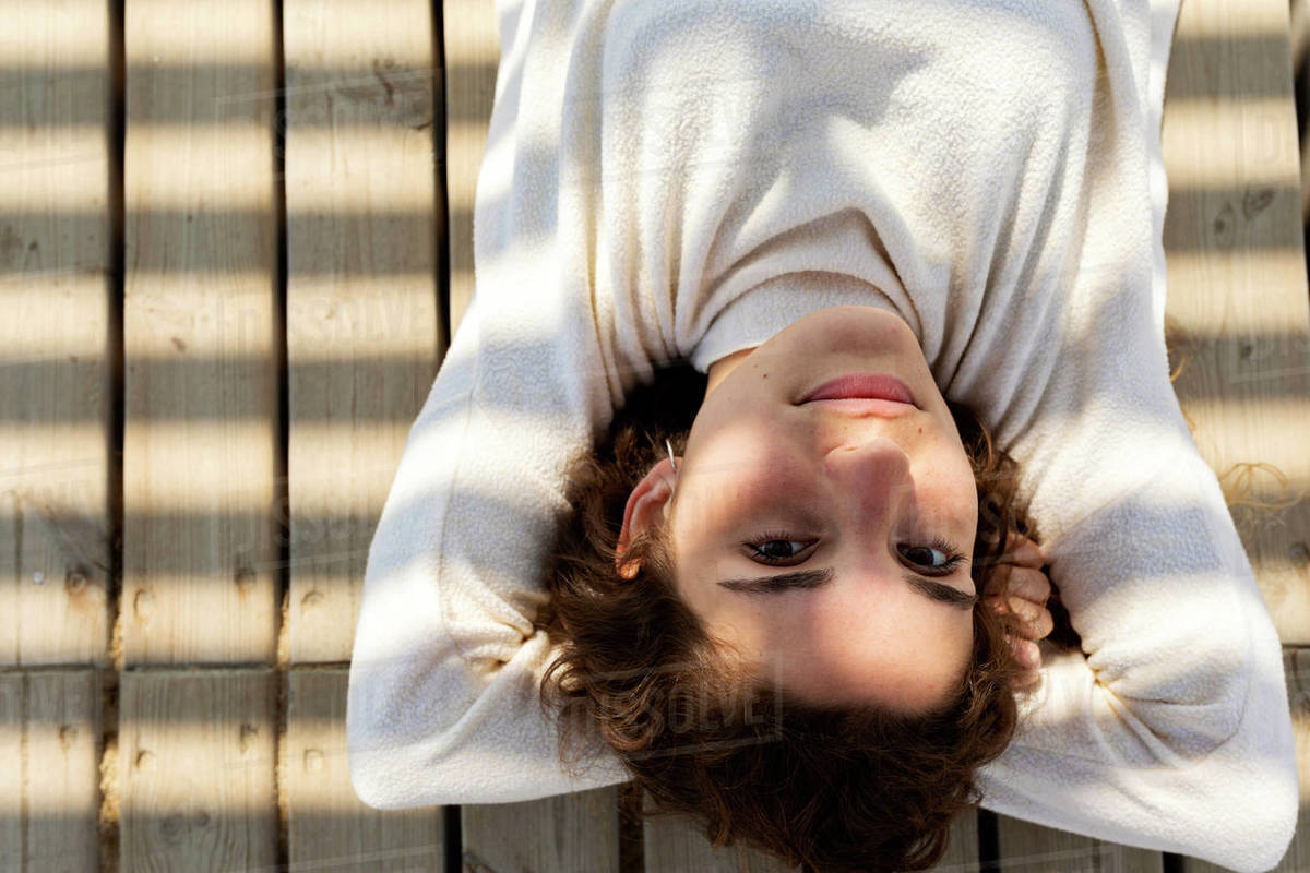 Young woman lays on wooden deck with  shadow cast over her face Royalty-free stock photo