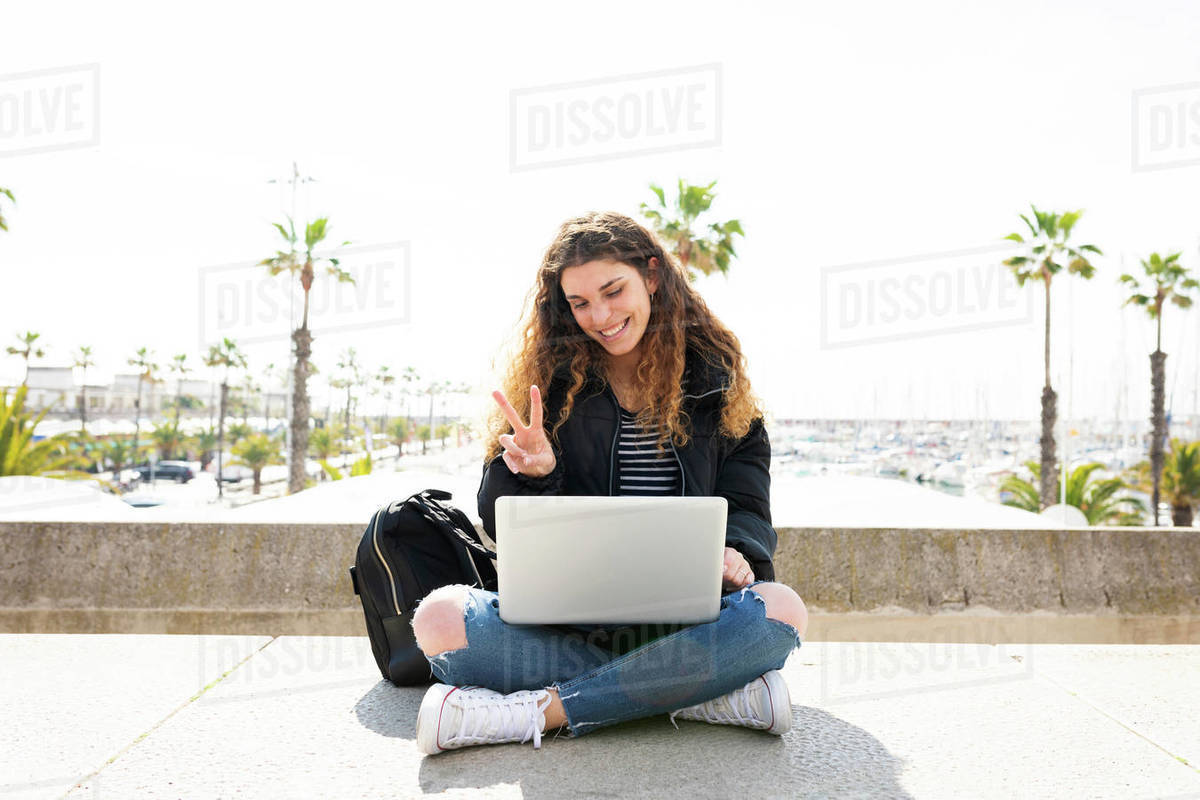 Young student sitting on stairs in the city port on a video call Royalty-free stock photo