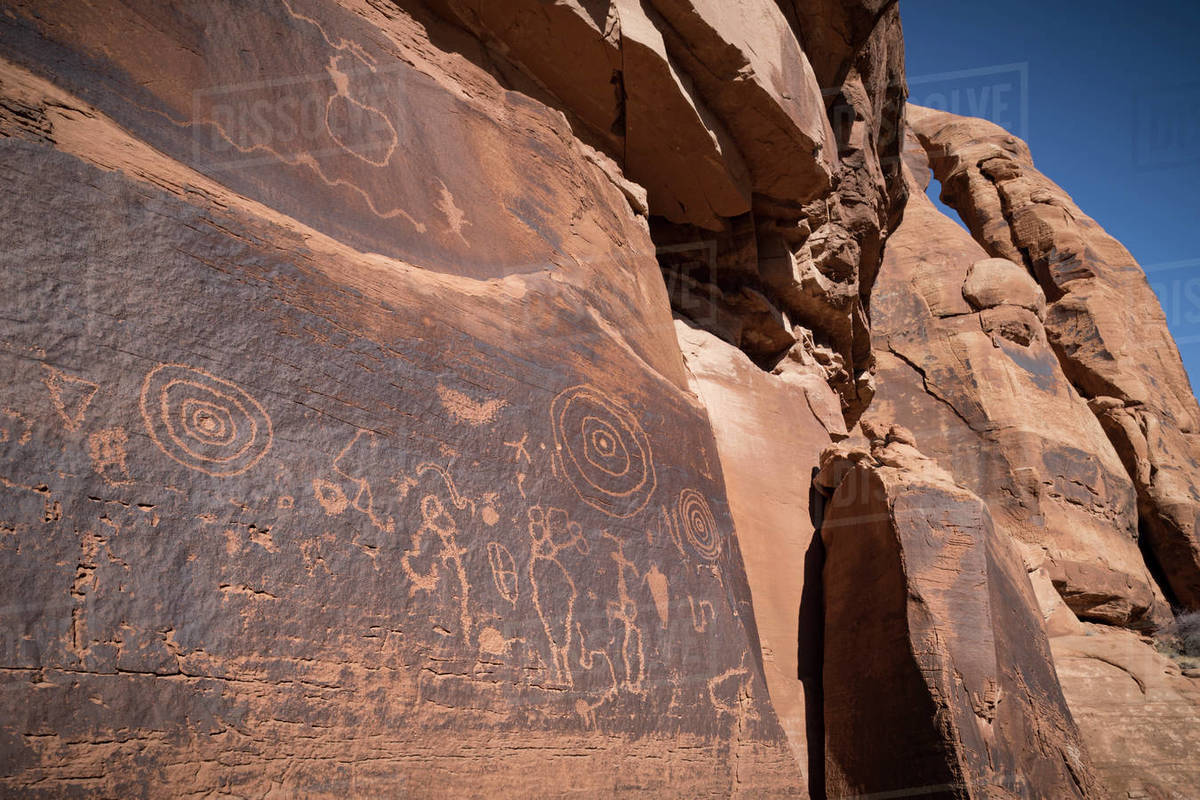 Native American petroglyphs etched onto sandstone rock wall below arch Royalty-free stock photo