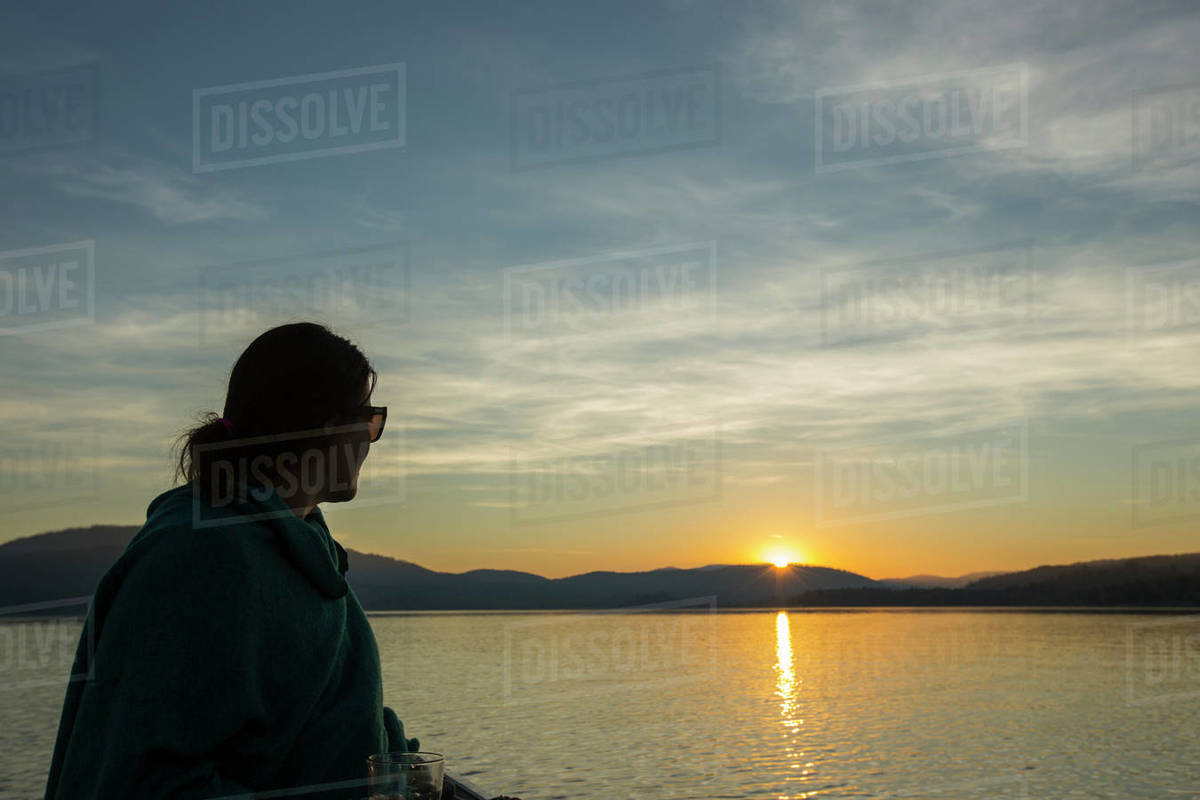 Woman watching a sunset from a canoe on Lake Pend Oreille, Idaho. Royalty-free stock photo
